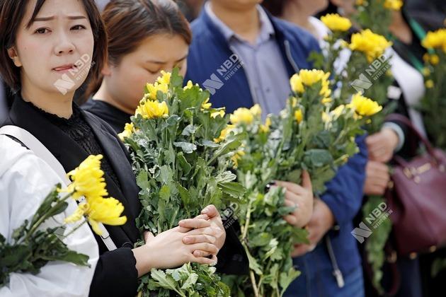 手捧黄菊的送别者,他们大多选择站在路边目送.
