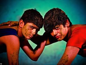 """近期电影《摔跤吧!爸爸》热映,影片讲述了前摔跤好手马哈维亚训练自己的两个女儿成为优秀摔跤手的故事。在印度,女性从事摔跤行业是一件非常""""出格""""的事情,然而印度哈里亚纳邦的两姐妹Khushi Ahlawat和Mansi Ahlawat便挑战了这样的""""规矩"""",她们和其他78名胸怀抱负的摔跤手在哈里亚纳邦东南部城市罗塔克的Sir Chotu Ram体育场接受训练。(图片来源:视觉中国)"""